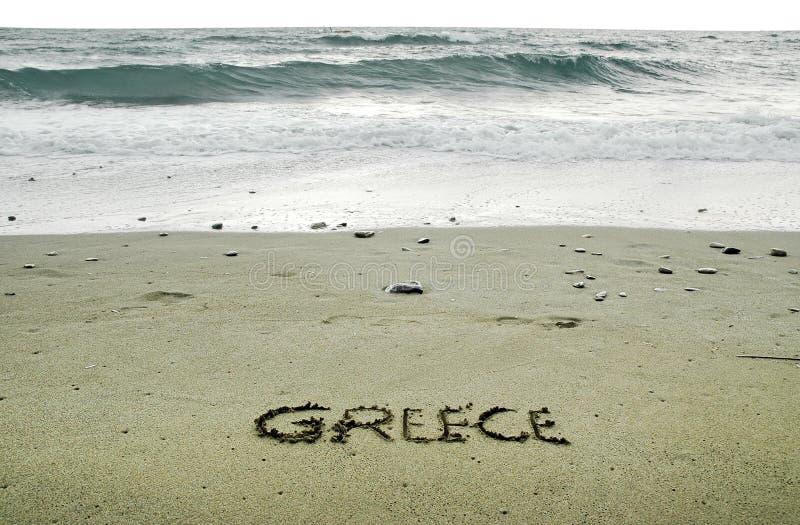 Grekland som är skriftlig i sand royaltyfri foto