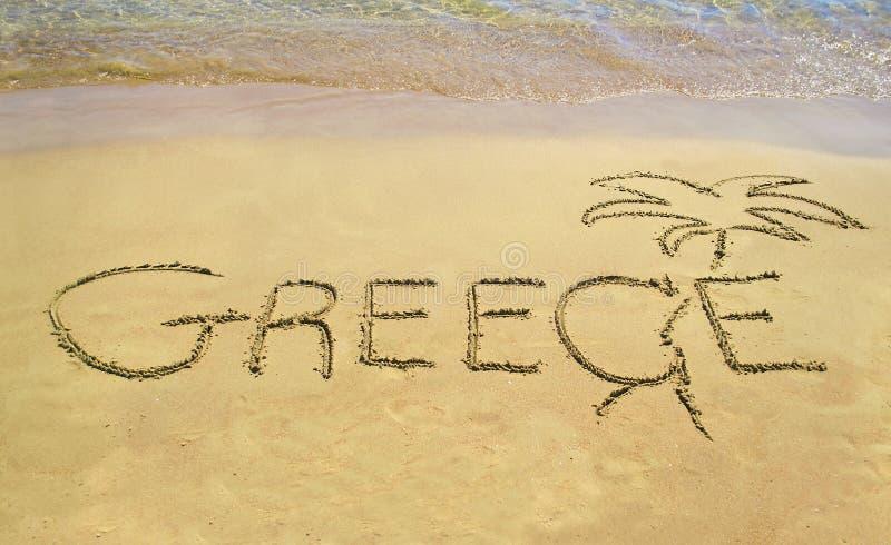 Grekland som är skriftlig på sand - sandpappra anmärkningssymbolen arkivbild