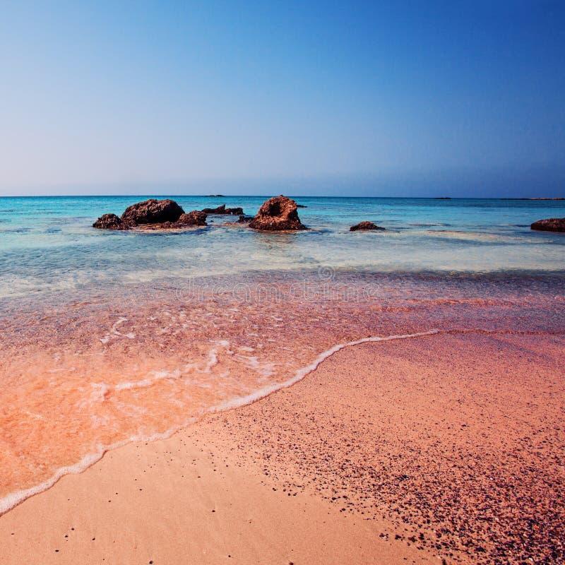Grekland Vågen av havet på den rosa sanden arkivfoton