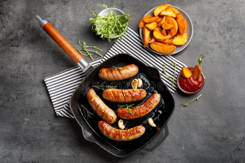 Grelhe a bandeja com as salsichas grelhadas deliciosas no fundo fotos de stock