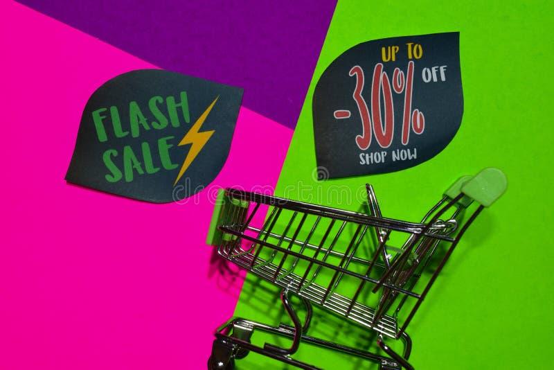 Greller Verkauf bis 30% weg vom Geschäfts-jetzt Text und dem Einkaufswagen stockfotos