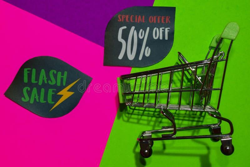 Greller Verkaufs-Sonderangebot 50% weg vom Geschäfts-jetzt Text und dem Einkaufswagen lizenzfreies stockbild