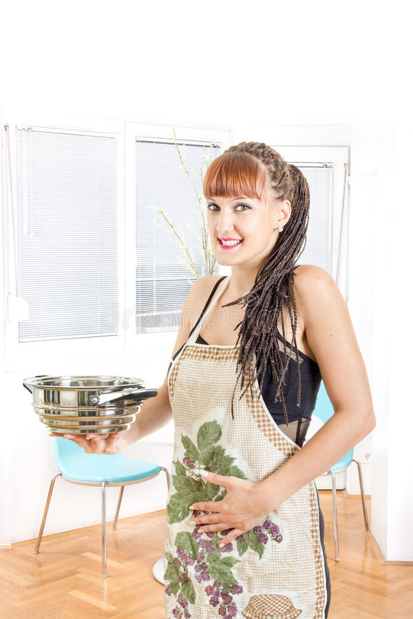 Grembiule d'uso della casalinga incinta dei giovani nel sorridere della cucina immagine stock