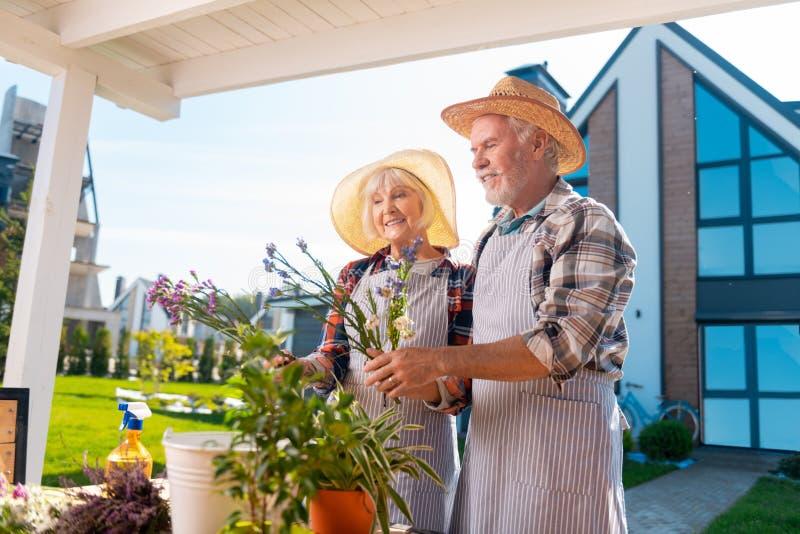 Grembiuli a strisce d'uso maturi della donna e dell'uomo che prendono cura dei fiori e delle piante fotografia stock libera da diritti