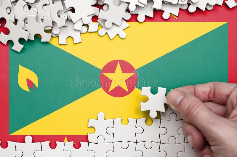 Grenada flag is depicted on a table on which the human hand folds a puzzle of white color stock photo