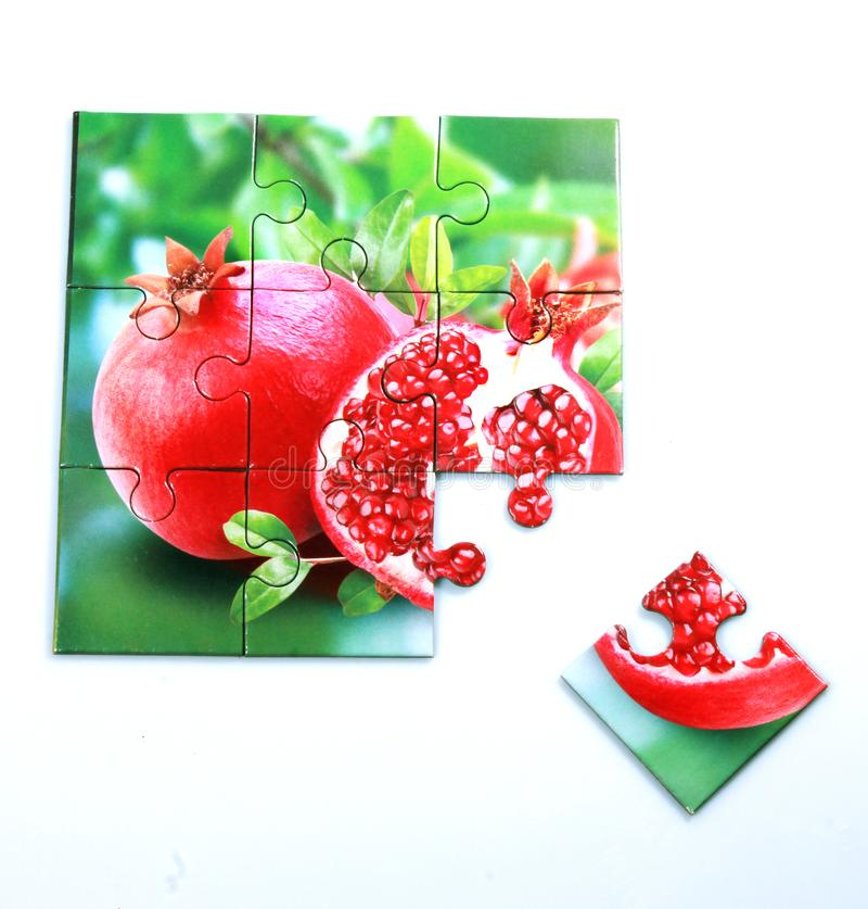 Grenade juteuse et sa moitié avec la photo de feuilles sur des conseils de puzzle photographie stock libre de droits