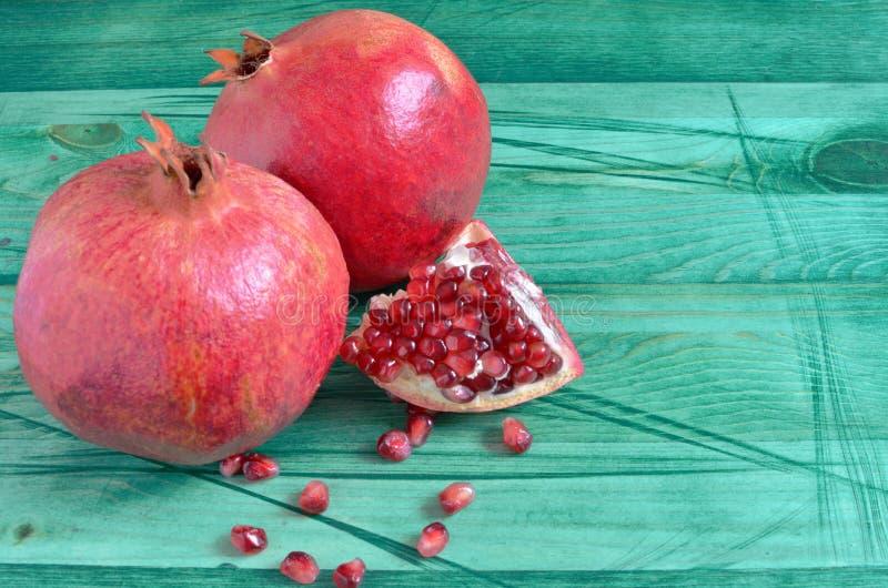 Grenade juteuse rouge de fruit avec les graines rouges sur le fond en bois vert images libres de droits