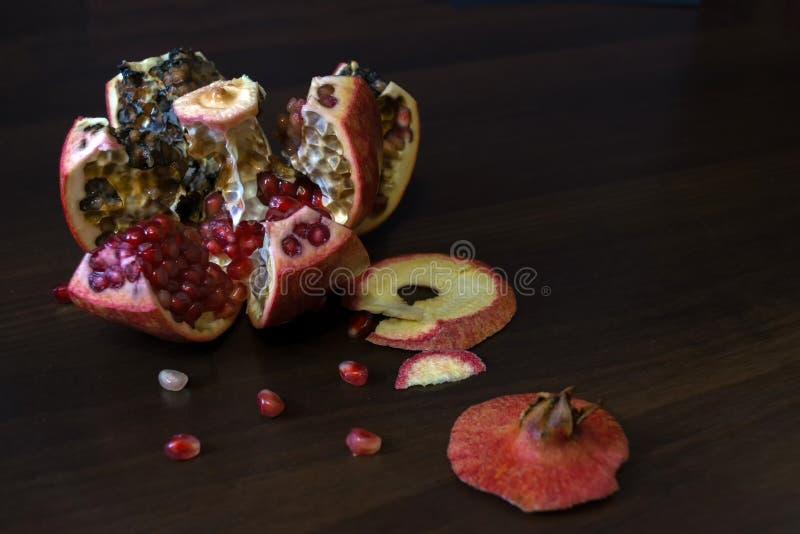 Grenade rouge putréfiée, corrompue, polie sur une table en bois avec des graines image stock