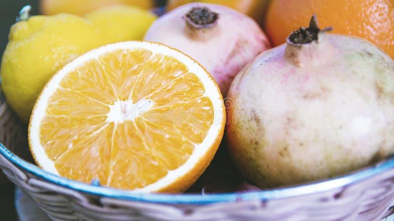 Grenades, oranges et citrons dans un panier mauvais sur une table en bois d'une cuisine rustique Fond d'automne image libre de droits