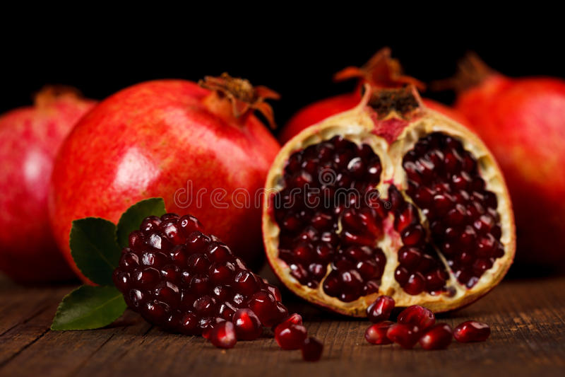 Grenadine fruits and seeds on wooden table. Grenadine fruits and seeds with small green leaf on rustic wooden table royalty free stock photography