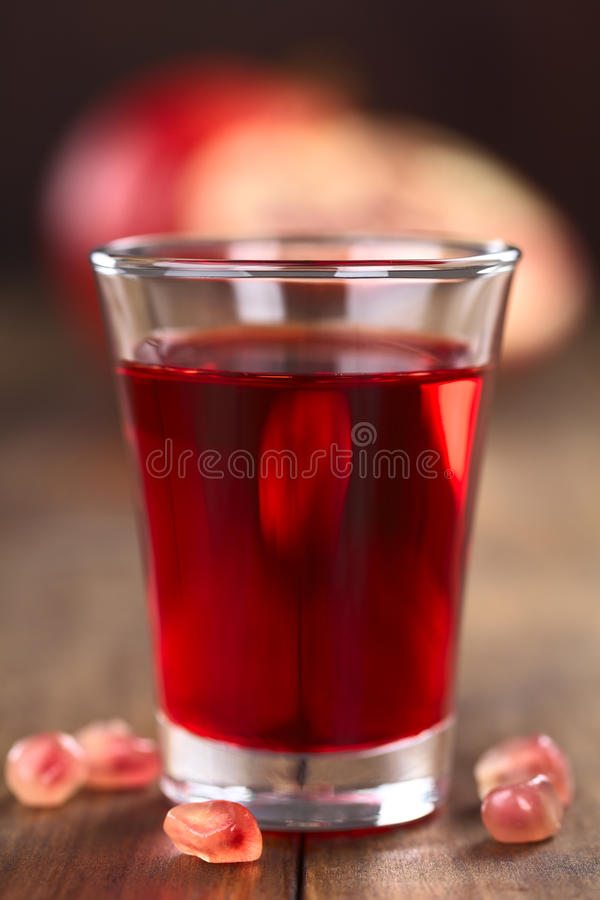 Grenadine Syrup. In shot glass with pomegranate seeds on the side and pomegranate in the back (Selective Focus, Focus on the front rim of the glass stock images