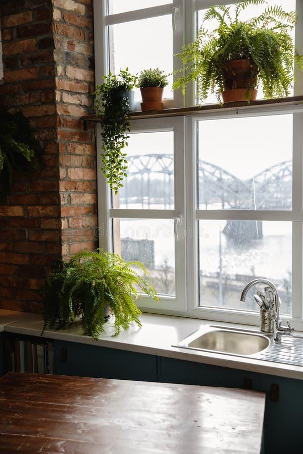 Grenier de cuisine avec le mur de briques conçu et une fenêtre faisant face au pont de chemin de fer à Riga, Lettonie photos stock