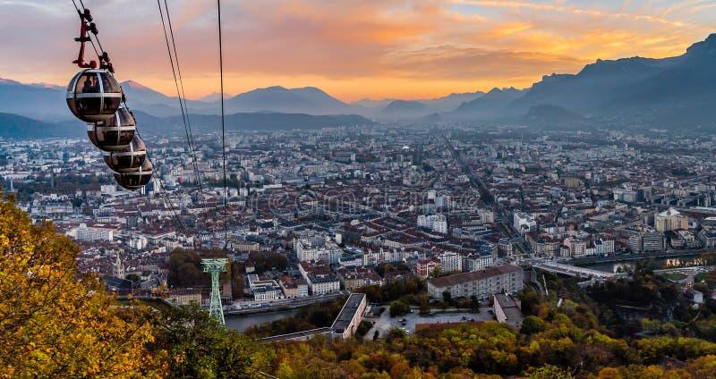 Grenoble y teleféricos en la puesta del sol fotos de archivo