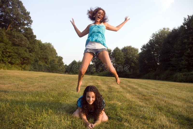 Grenouille de saut de pièce de deux filles photos stock