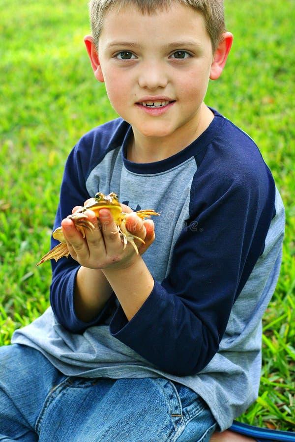 Grenouille mignonne de fixation de petit garçon photographie stock