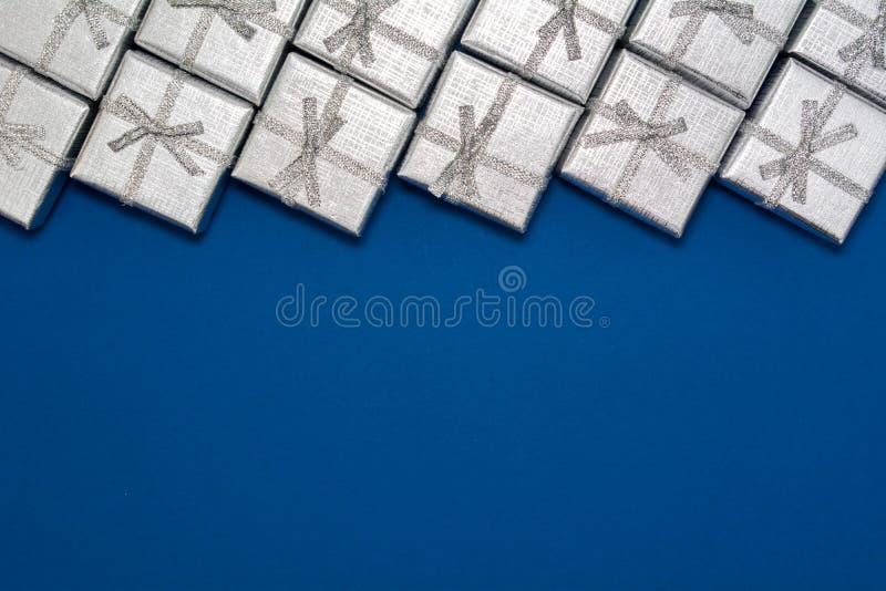 Grens van zilveren glanzende giften op blauwe achtergrond Nieuw jaar ` s en Kerstmisdecoratie stock foto's