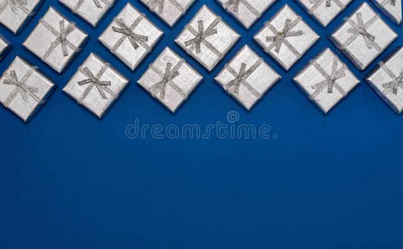 Grens van zilveren glanzende giften op blauwe achtergrond Nieuw jaar ` s en Kerstmisdecoratie royalty-vrije stock fotografie