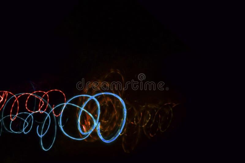Grenze von blauen und orange leuchtenden NeonSpiralen auf einem schwarzen BAC lizenzfreie abbildung