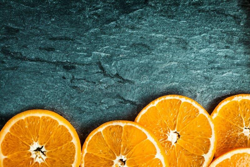 Grenze von bunten orange Scheiben auf Schiefer lizenzfreie stockfotografie