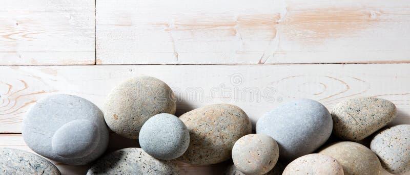 Grenze von grauen Zensteinen stellte auf weißen hölzernen Hintergrund ein stockfoto