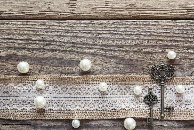 Grenze von Leinwand mit weißer Spitze, Weinleseschlüsseln und Perlen auf altem lizenzfreie stockbilder