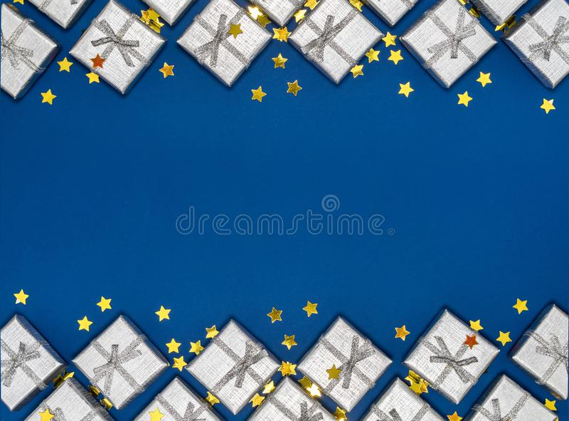 Grenze von silbernen glänzenden Geschenken und von goldenen Sternen auf blauem Hintergrund Ökologische, hölzerne Weihnachtsdekora stockbild