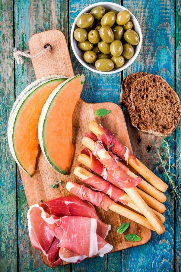Gressins avec le prosciutto, le melon, les olives et le pain images libres de droits