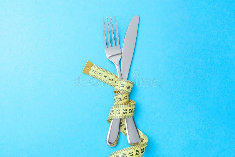 Greve da fome como a maneira de perder o peso A forquilha e a faca são envolvidas na fita de medição amarela no azul fotos de stock royalty free