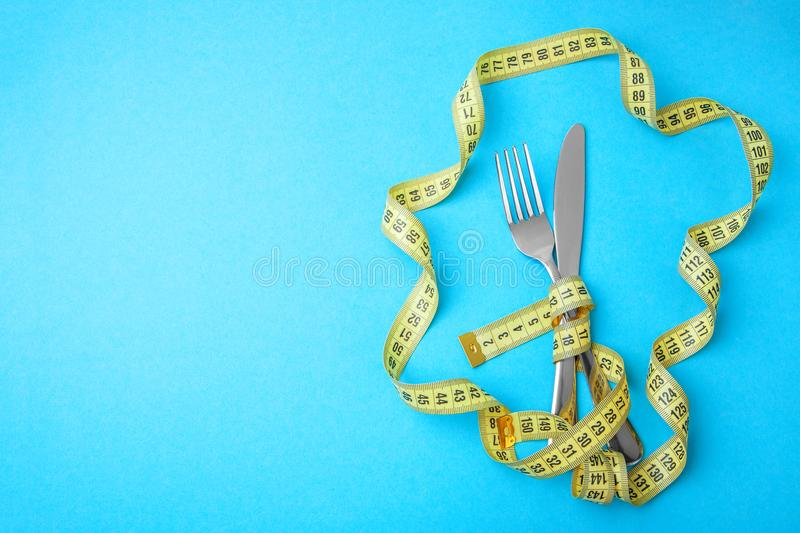 Greve da fome como a maneira de perder o peso A forquilha e a faca são envolvidas na fita de medição amarela no fundo azul foto de stock royalty free