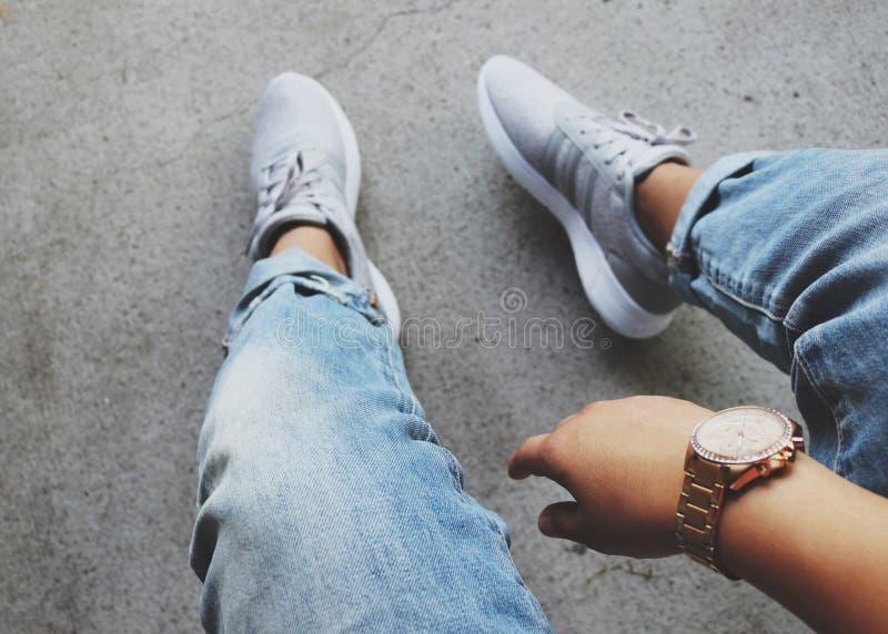 Grey Adidas Sneakers Near Blue Denim Bottoms stock photography