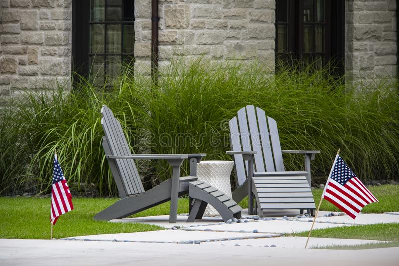 Two grey Adirondack chairs sitting on a small patio with table between them in front of tall decorative grass and windows of rock royalty free stock photo