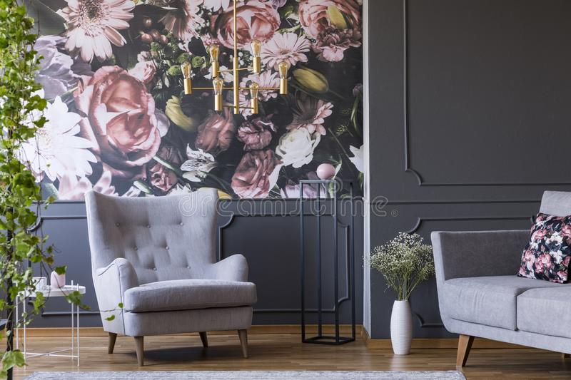 Grey armchair against flowers wallpaper in dark living room interior with sofa and plant. Real photo. Concept royalty free stock photography