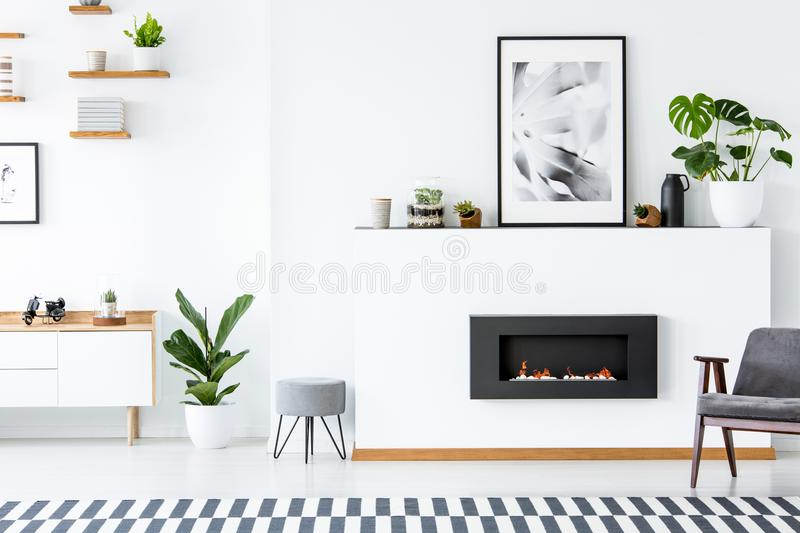 Grey armchair next to fireplace under poster in living room interior with plant and stool. Real photo stock images
