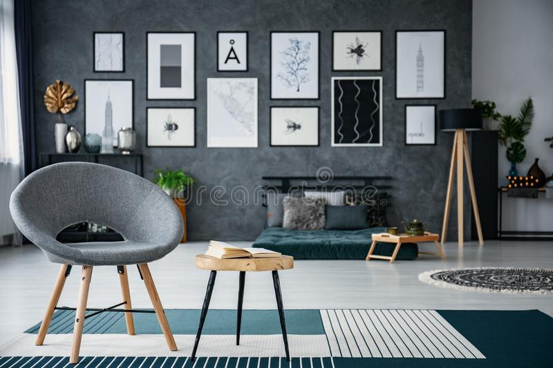 Grey armchair next to table on carpet in living room interior with gallery of posters. Real photo with blurred background. Concept stock photos