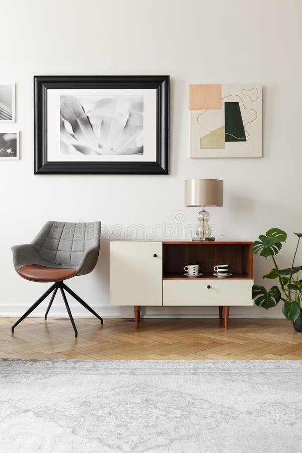 Grey armchair next to white cabinet with lamp in modern loft interior with posters. Real photo. Concept stock photo