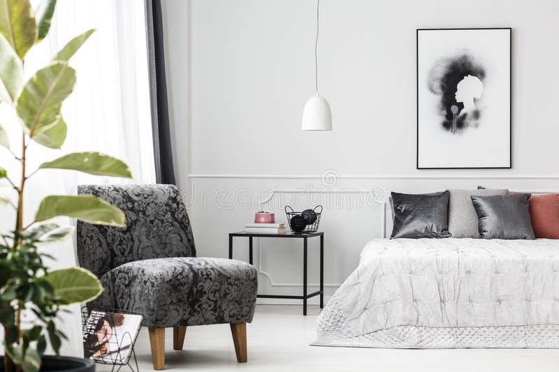 Grey armchair in bedroom royalty free stock photography