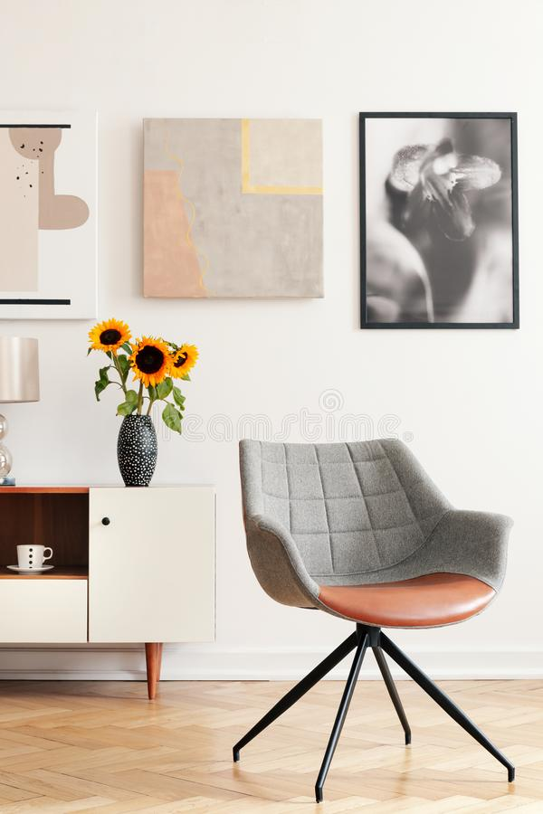 Grey armchair and sunflowers on cabinet in white living room interior with posters. Real photo stock photo