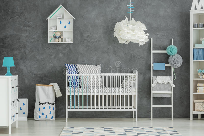 Grey baby bedroom with cot royalty free stock photo