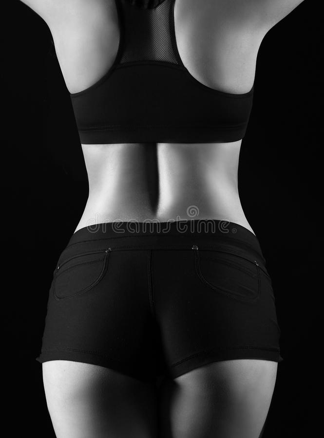 Grey back. Young athletic girl on a dark background royalty free stock photo