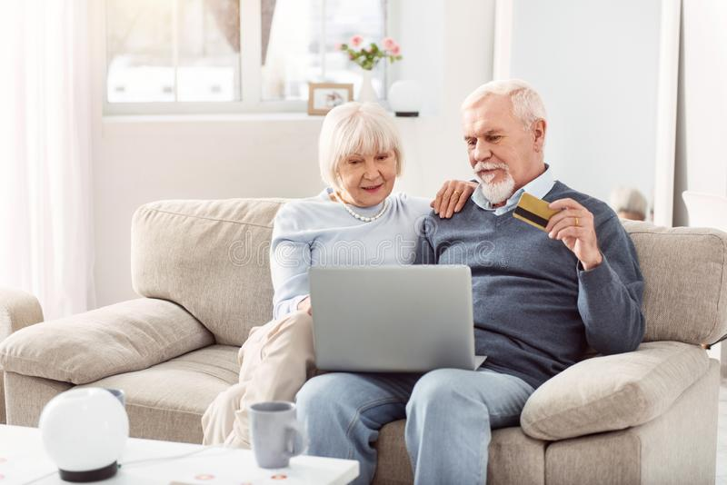 Grey-bearded man and short-haired woman making purchase online stock images
