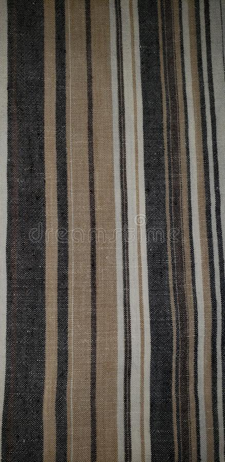 Grey and beige stripes. This is a picture of a textured linen fabric in neutral stripes. It can be used a neutral background royalty free stock photography
