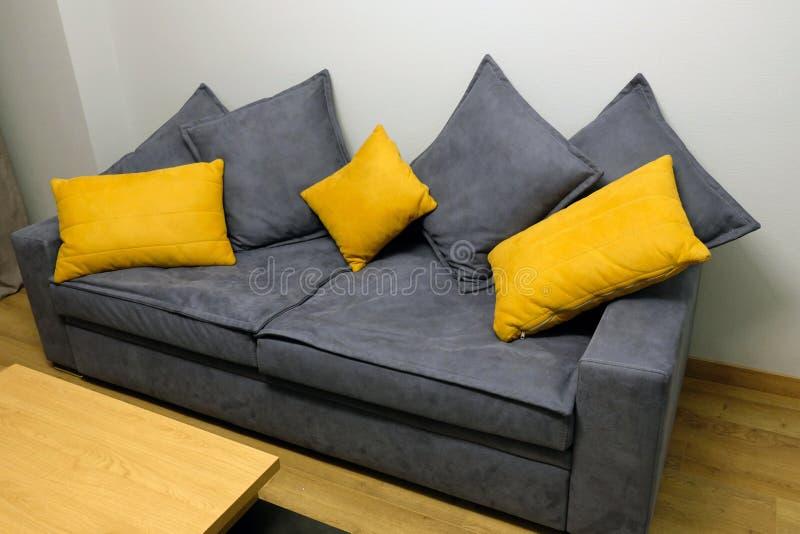 Grey big sofa with yellow and grey pillows. stock photography