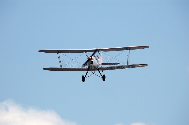 Grey biplane. An airshow with a grey biplane on a sunny day, few clouds royalty free stock photos