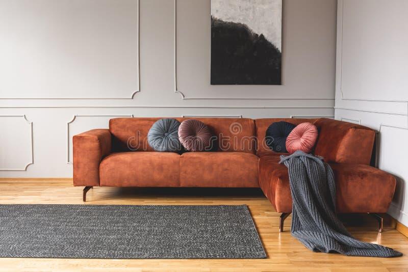 Grey, black, beige and pink round velvet pillows on ginger colored living room sofa. Grey, black, beige and pink round velvet pillows on ginger colored living stock images