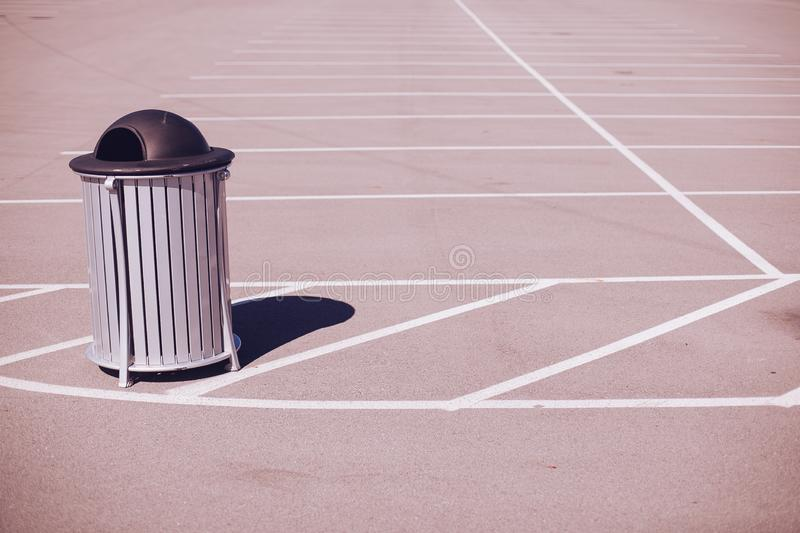 Grey Black Trash Can Empty Parking Lot White Lines Shadow royalty free stock photography
