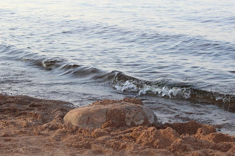 Grey with blue sea on a cold day, wave and sand royalty free stock images