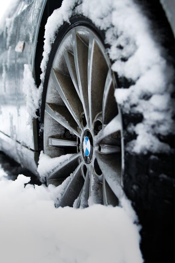 Серый обод BMW в снегу. Фотография серого обода BMW, частично покрытого снегом, с четко видимым логотипом Сток-фотография без роялти