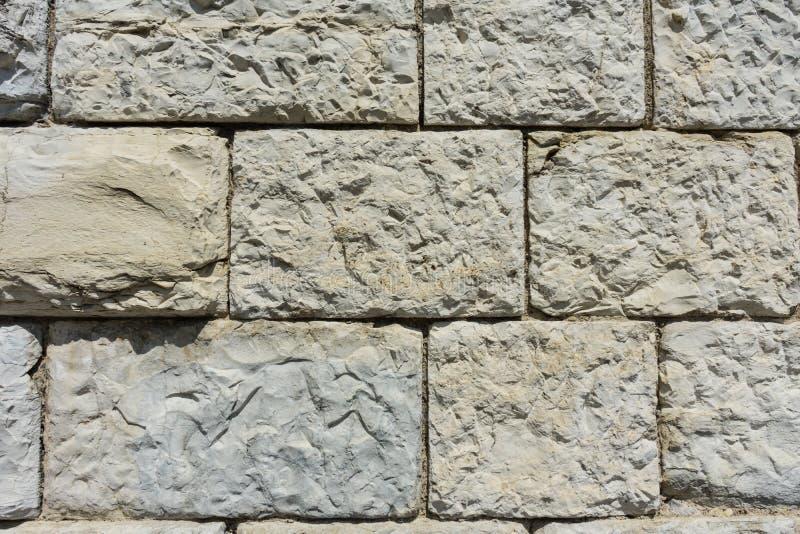 Grey brick wall with big stones. Grey brick wall close up old building stock image