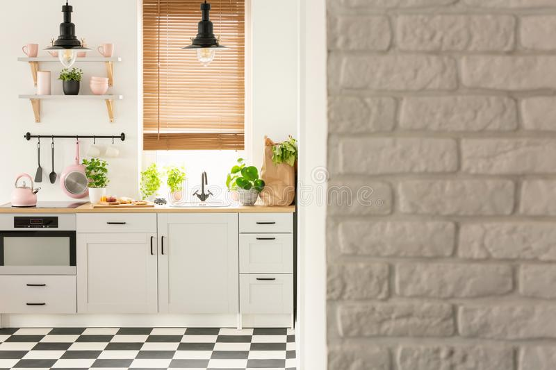 Grey brick wall in bright kitchen interior with lamps above coun stock photo