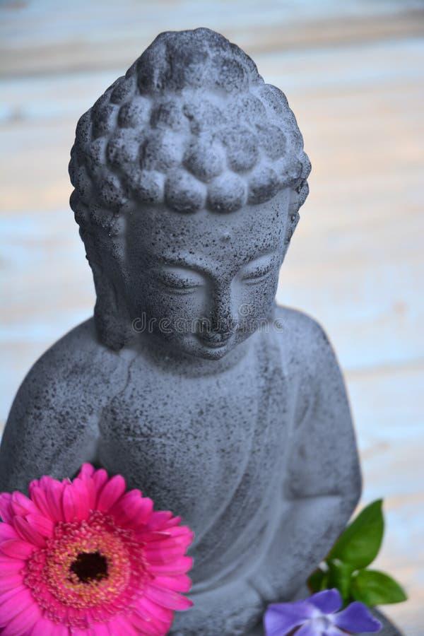 Grey Buddha staty med blommor och zenstenar royaltyfria bilder